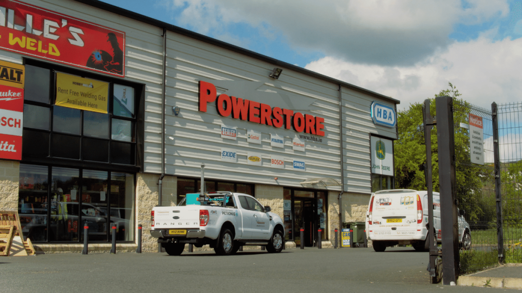HBA Powerstore Newry with company vehicles and automotive brand logos including Sealey, Exide, Bosch, and Castrol.